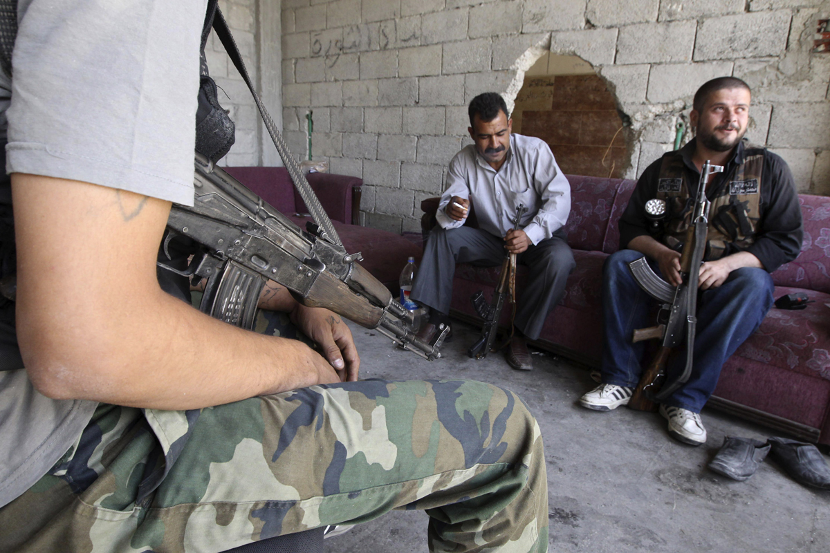 Free Syrian Army fighters carry their weapons as they sit at their guard post in Aleppo's Karm al-Jabal district